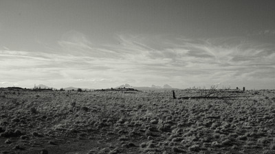 A classic black and white photo of a desert, mountains in the distance and whispy clouds.